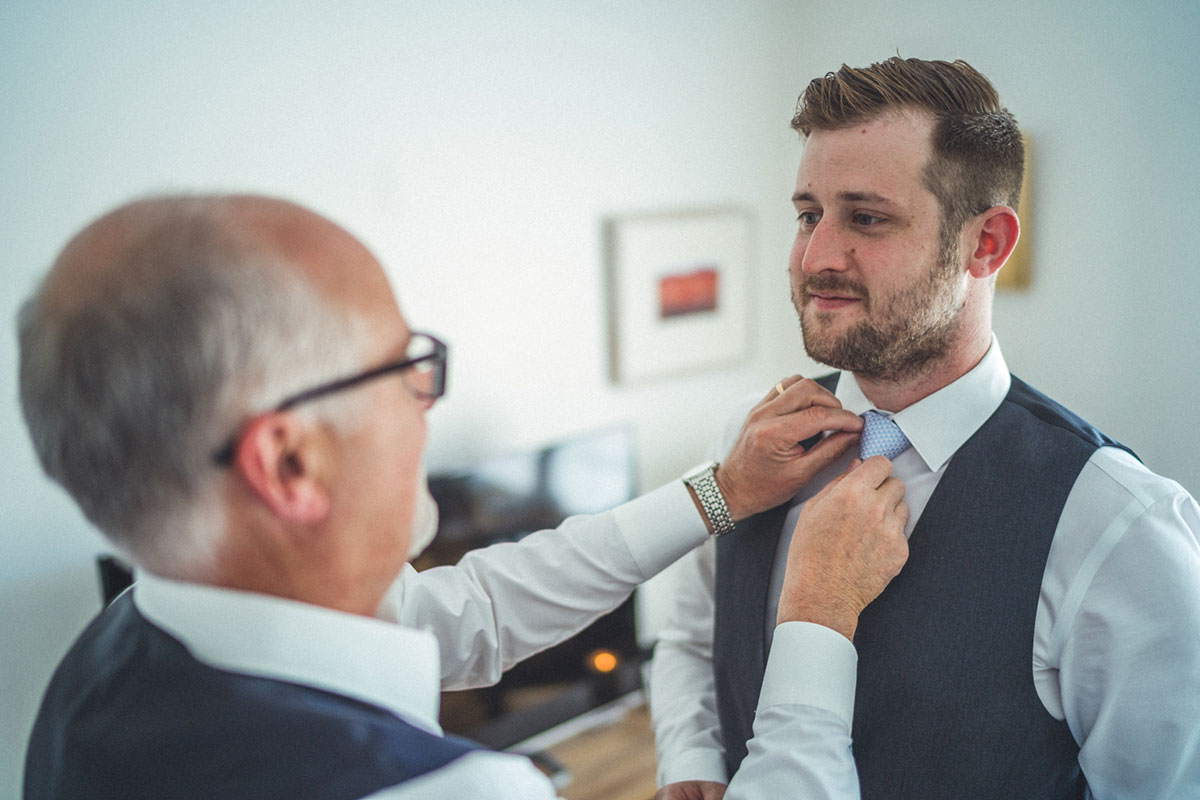 male helping a groom fix his tie on his wedding morning