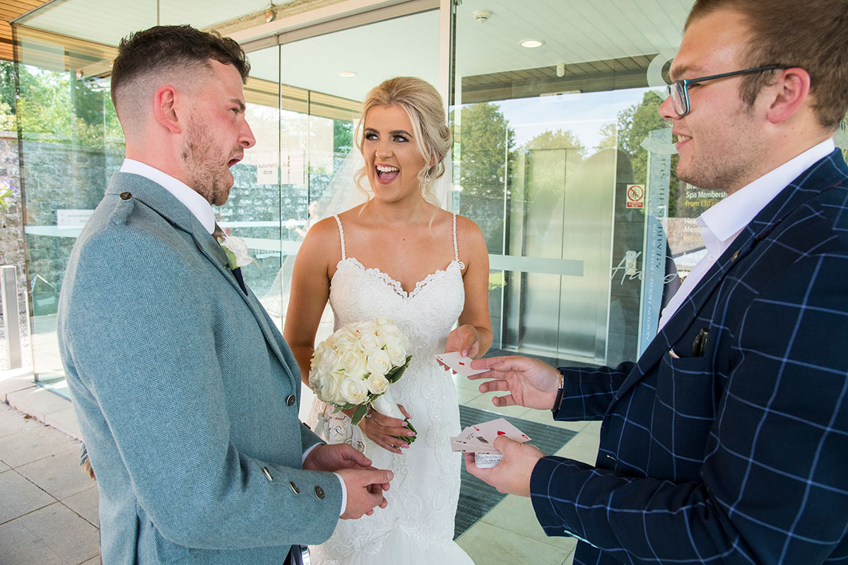bride and groom looking surprised as magician performs at card trick at their wedding