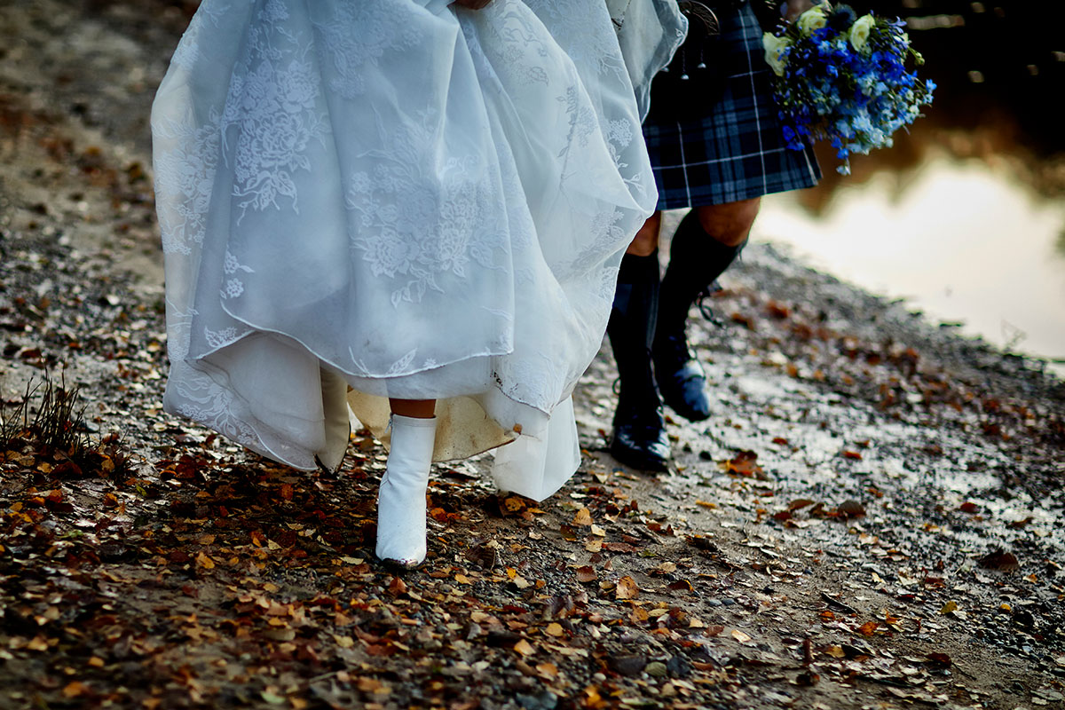 waist-down image of bride and groom walking along a stony beach with bride wearing white boots