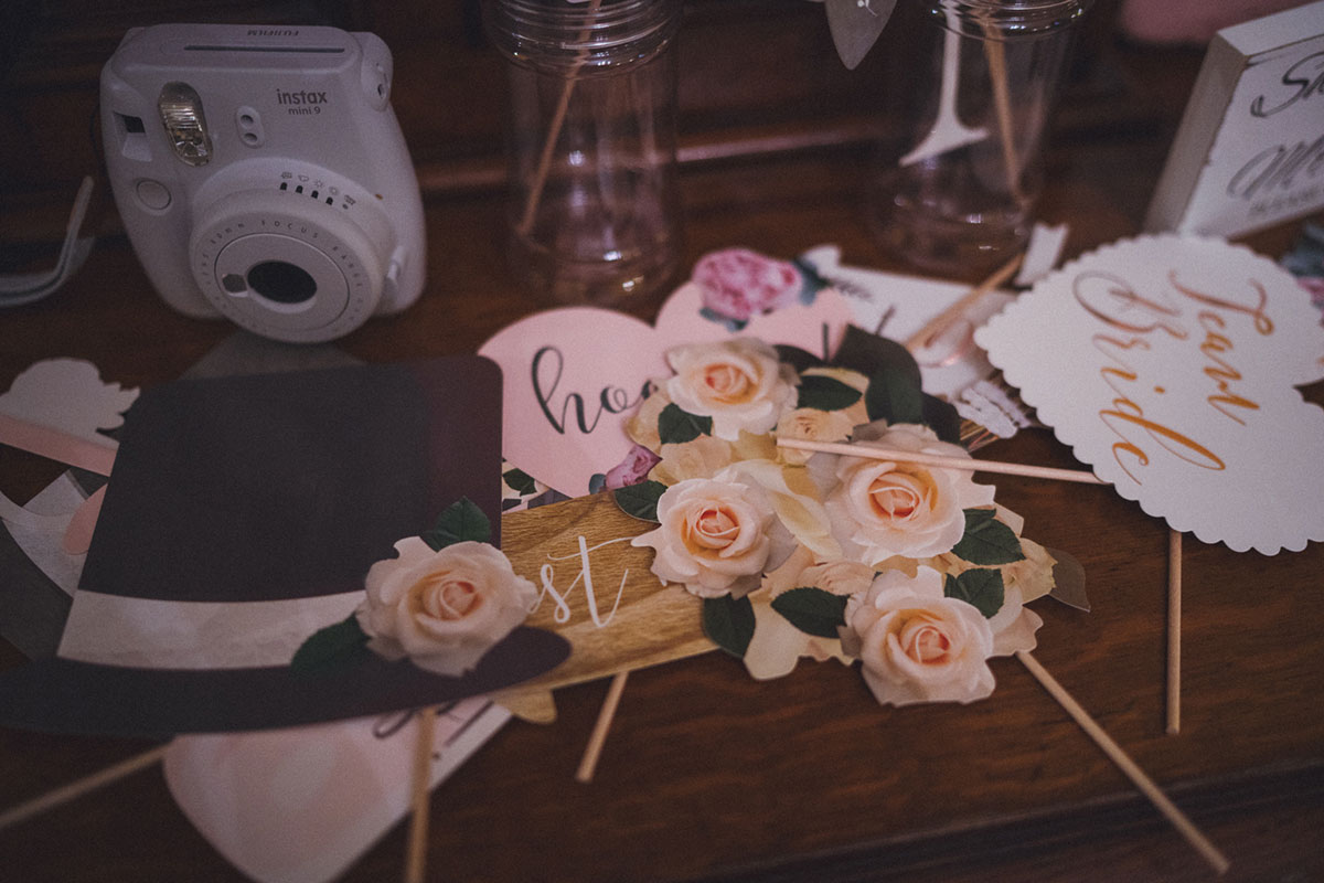 white Instax camera sitting on wooden table surrounded by floral and love heart paper photo booth props