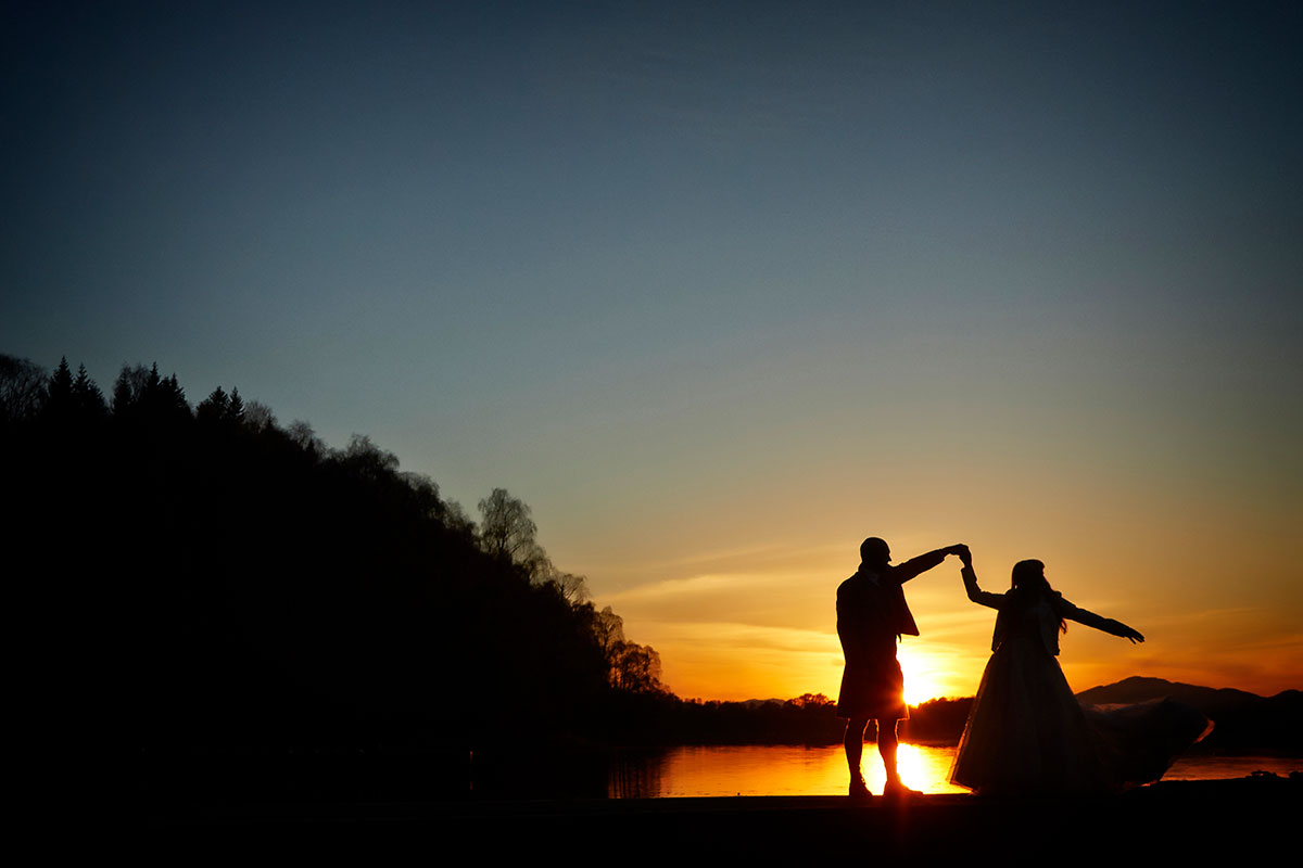 sunset silhouetted image of bride and groom dancing on the shore of Loch Insh