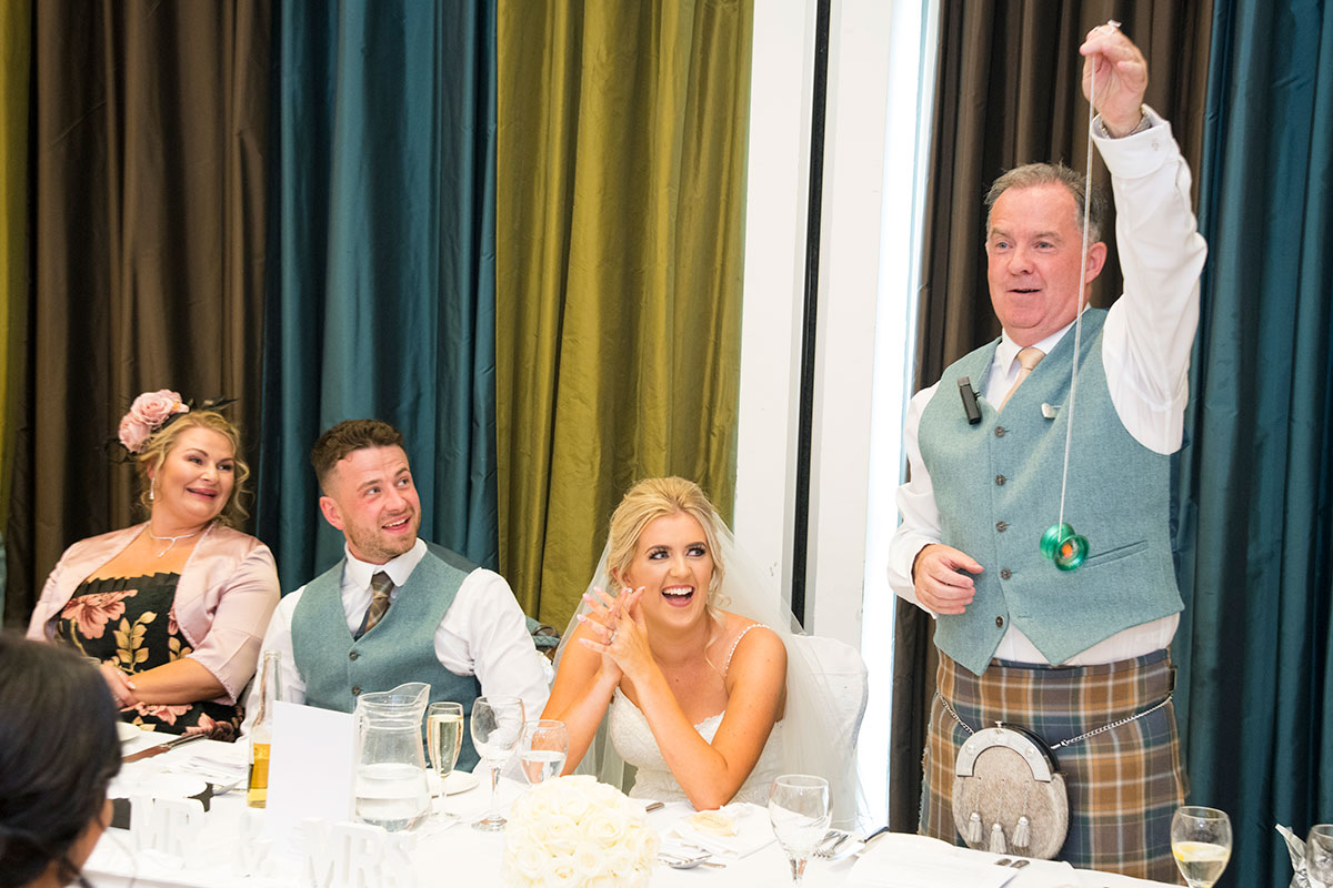 man wearing a kilt holding a yoyo during a wedding speech while bride, groom and top table guests laugh