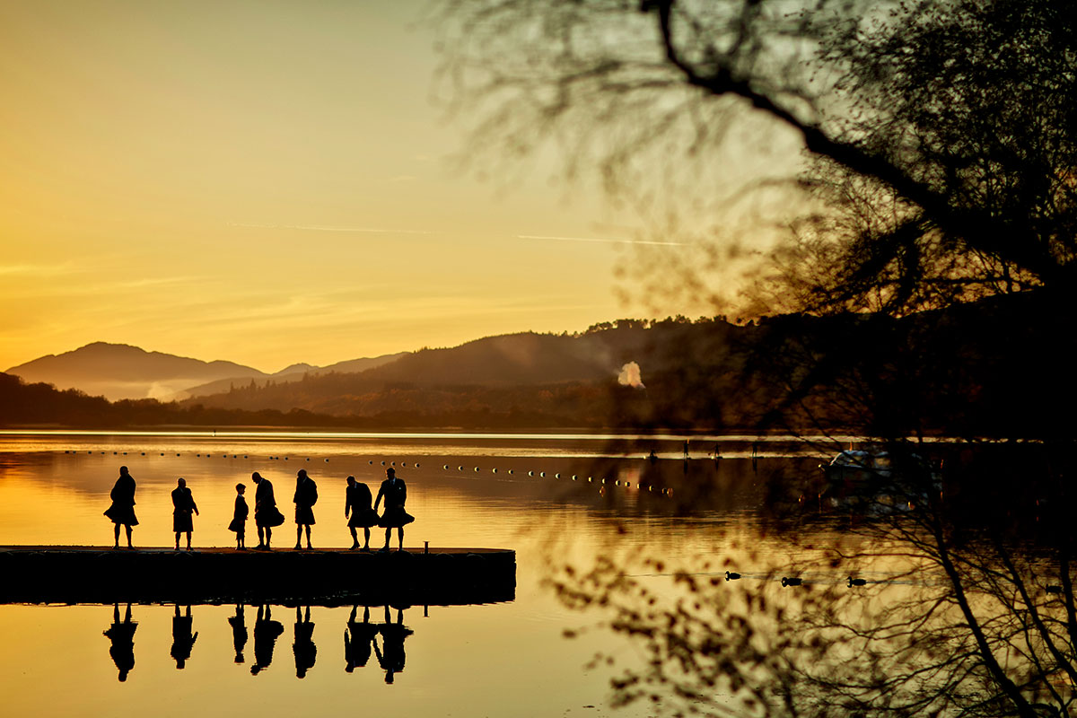 silhouette image of men wearing kilts standing on a pier at Loch Insh