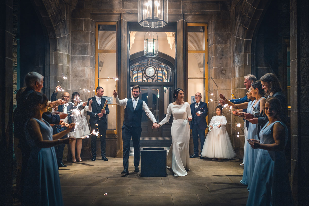 bride and groom at front entrance of Lews Castle carrying sparklers surrounded by guests also with sparklers