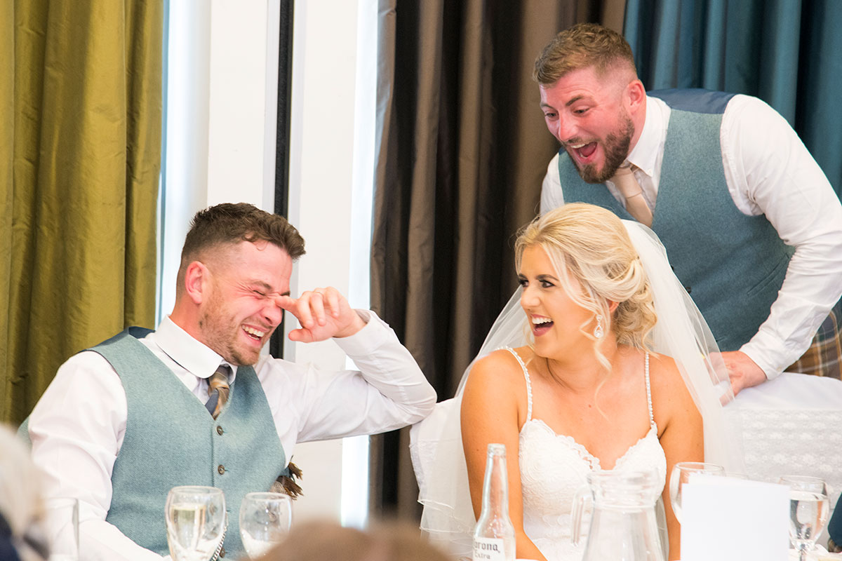 embarassed groom laughing with bride during best man's speech at wedding
