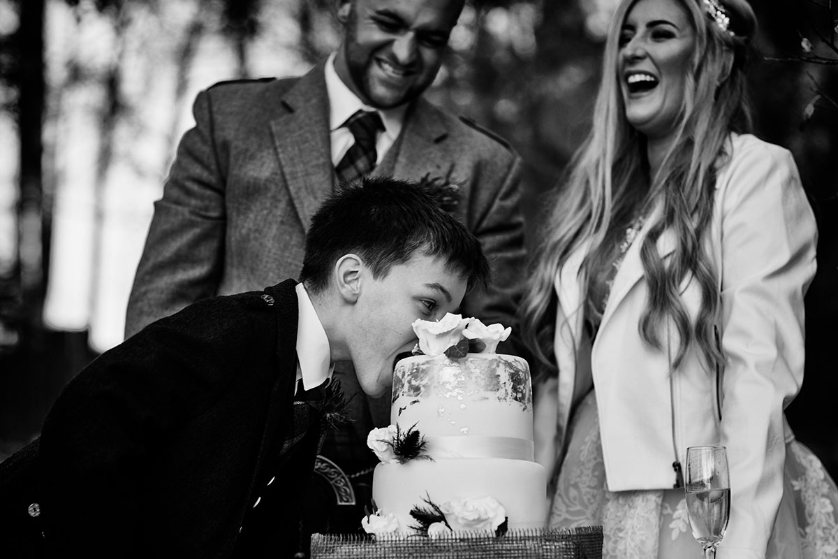 black and white image of bride and groom laughing as young male weddng guest bites into a wedding cake in front of them