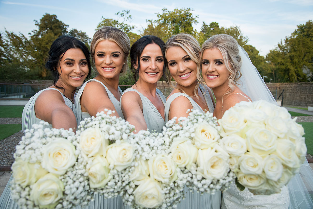bride and four bridesmaids posing and smiling holding white bouquets towards camera