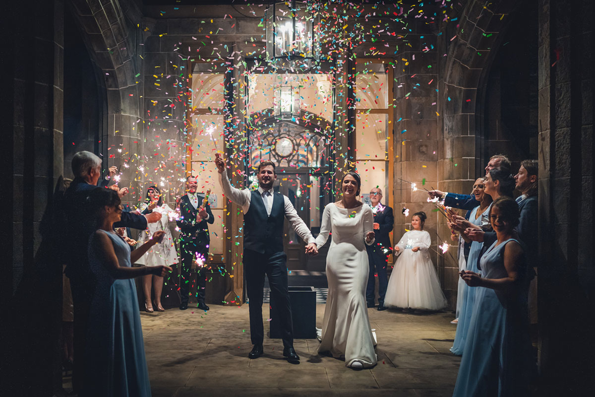 bride and groom holding sparklers and being showered in confetti while leaving Lews Castle