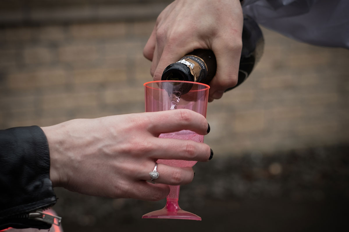 hand holding pink plastic wine glass while another hand pours in fizzy wine