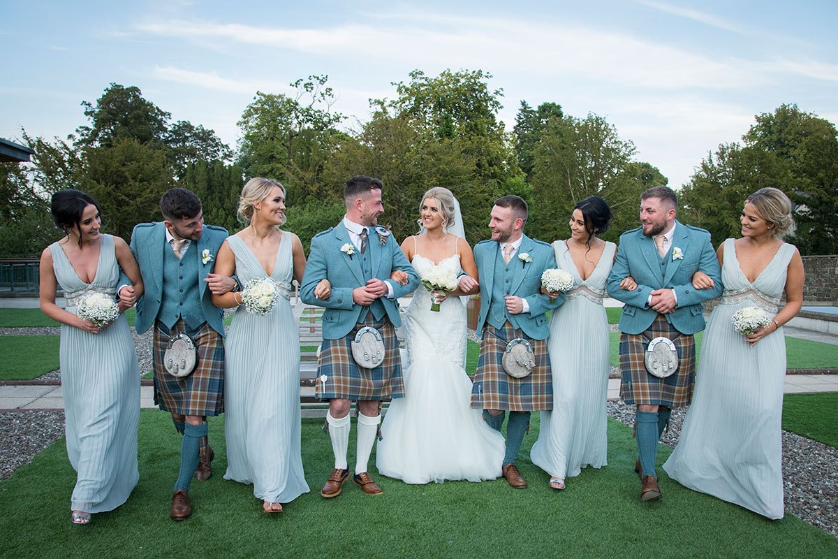 bride groom bridesmaids and best men linking arms and walking in garden at Norton House Hotel