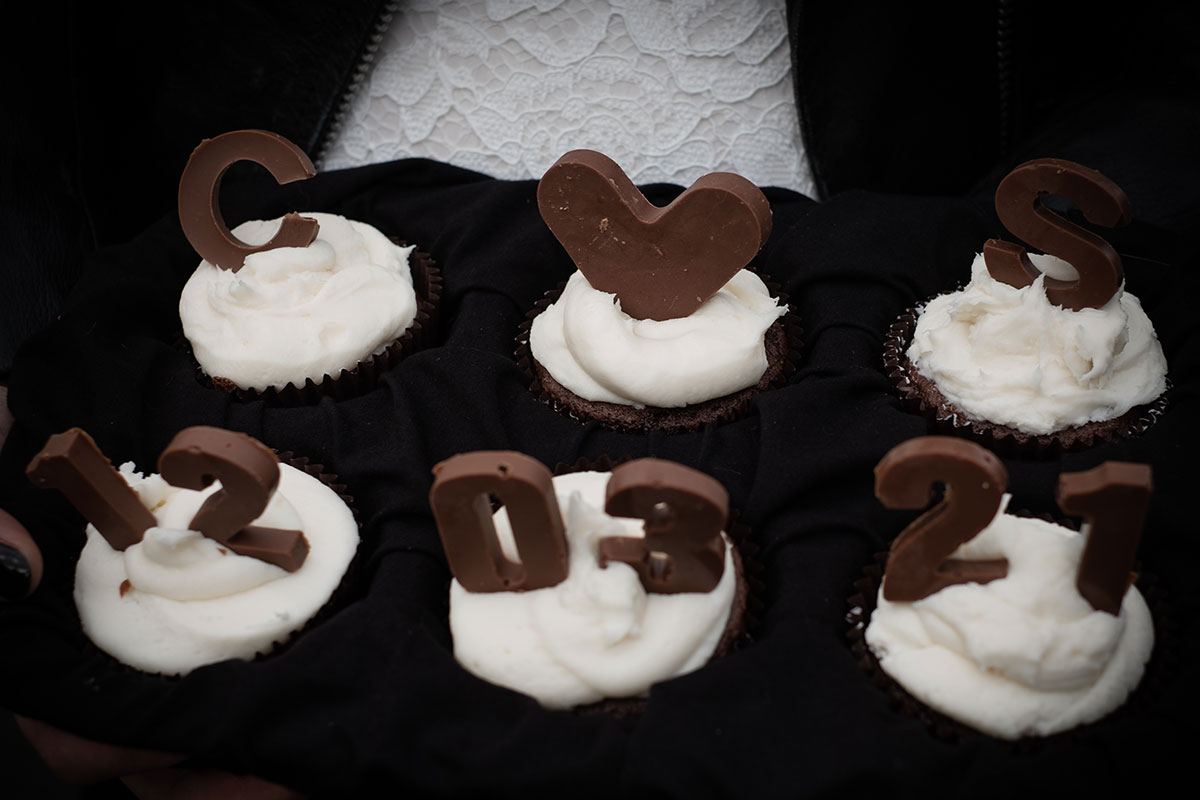 chocolate and white buttercream cupcakes with chocolate lettering spelling out wedding date and initials