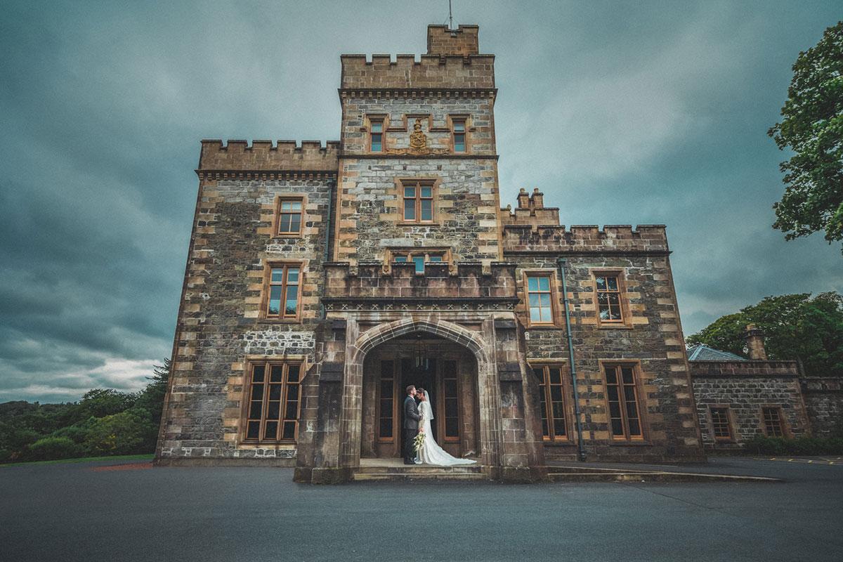 groom kissing bride on head while standing in doorway of Lews Castle