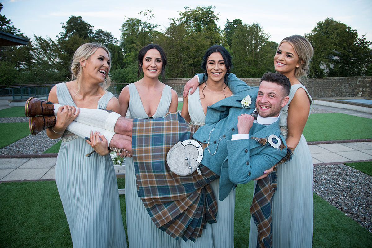four bridesmaids wearing pale blue beaded dresses carrying groom and laughing in garden of Norton House Hotel