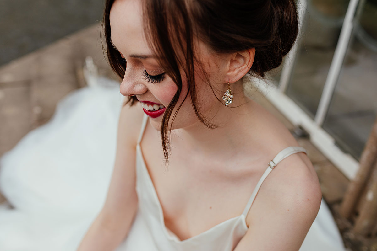 a close-up image of a bride sitting on the steps outside the Camellia House at Culzean Castle