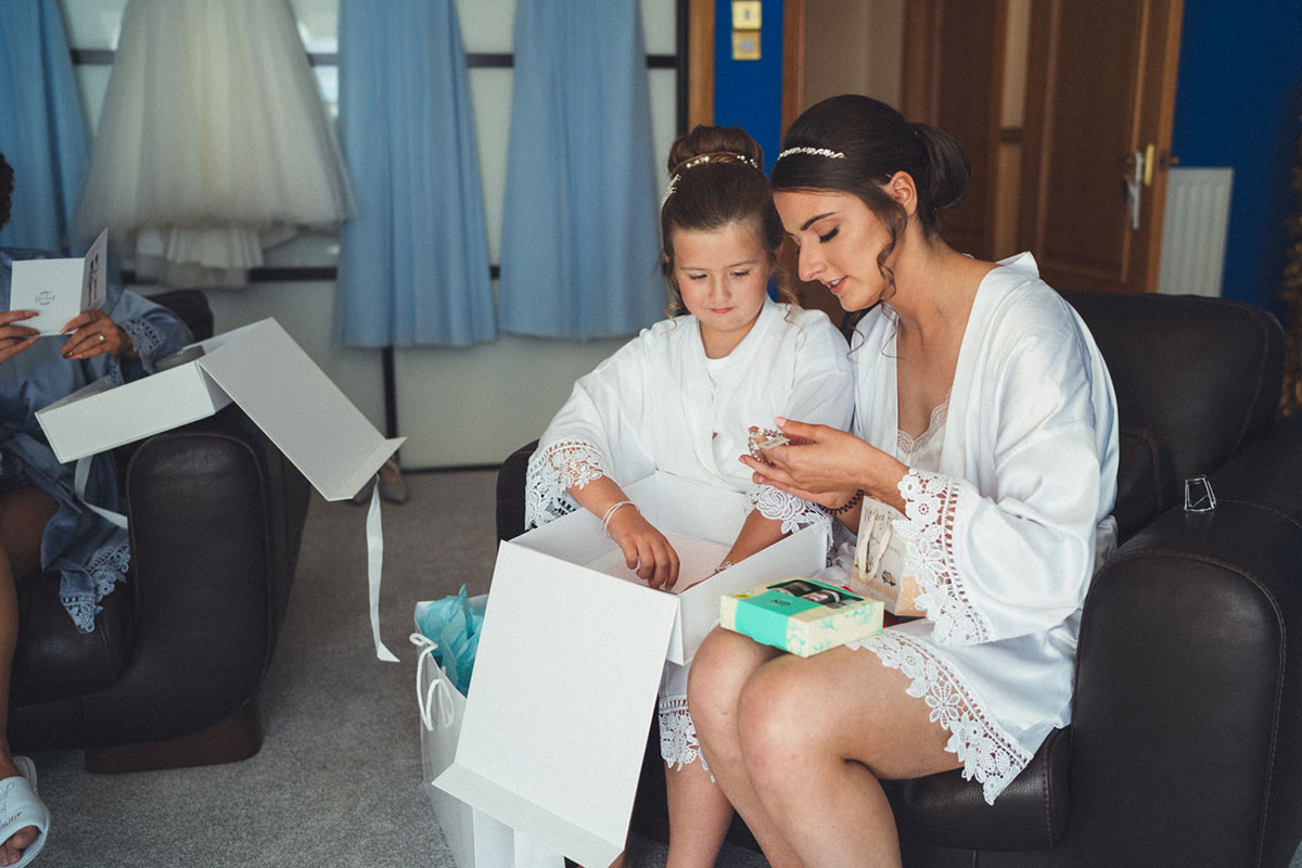 bride and flower girl wearing white dressing gowns and opening present on wedding morning