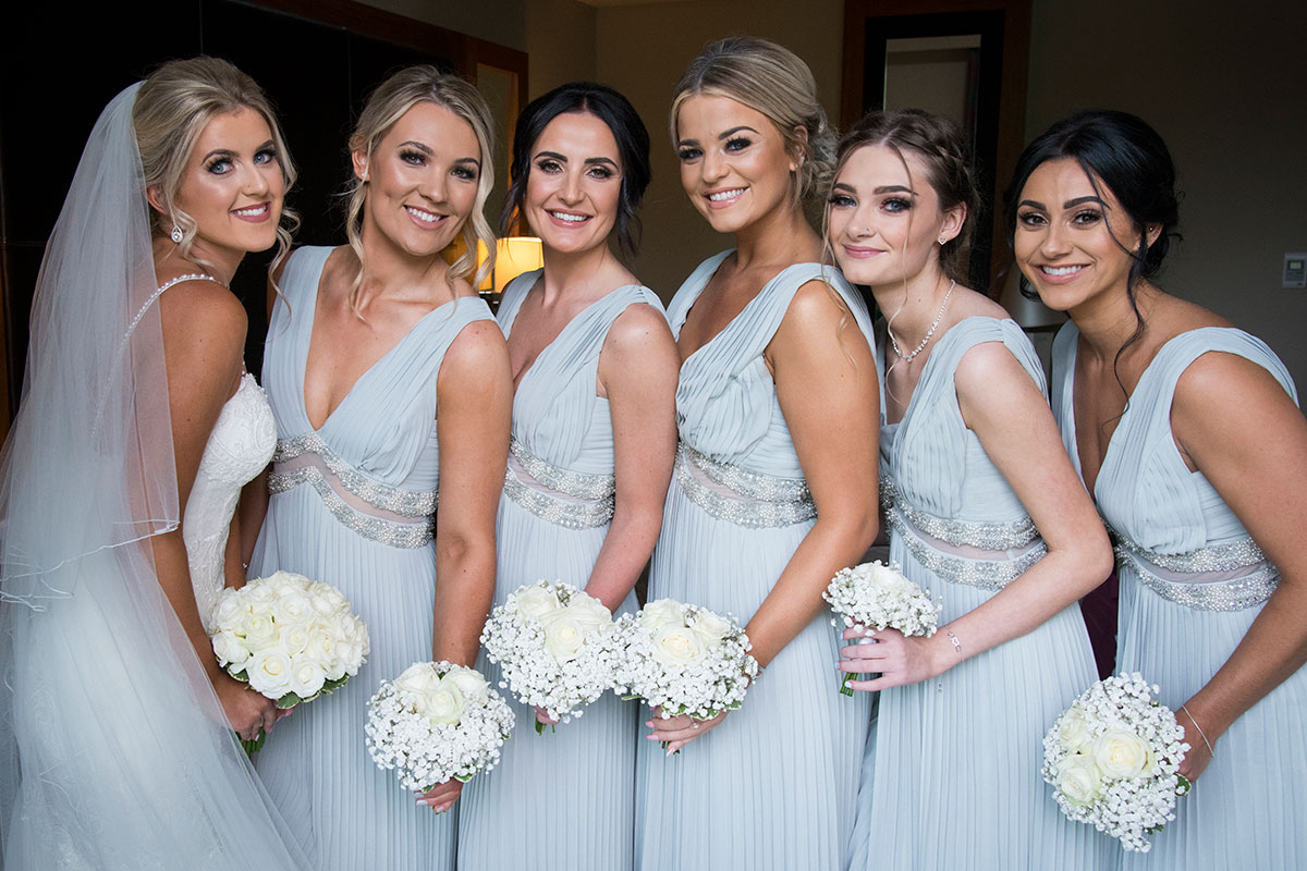a bride and five bridesmaids wearing pale blue beaded dresses posing for a picture