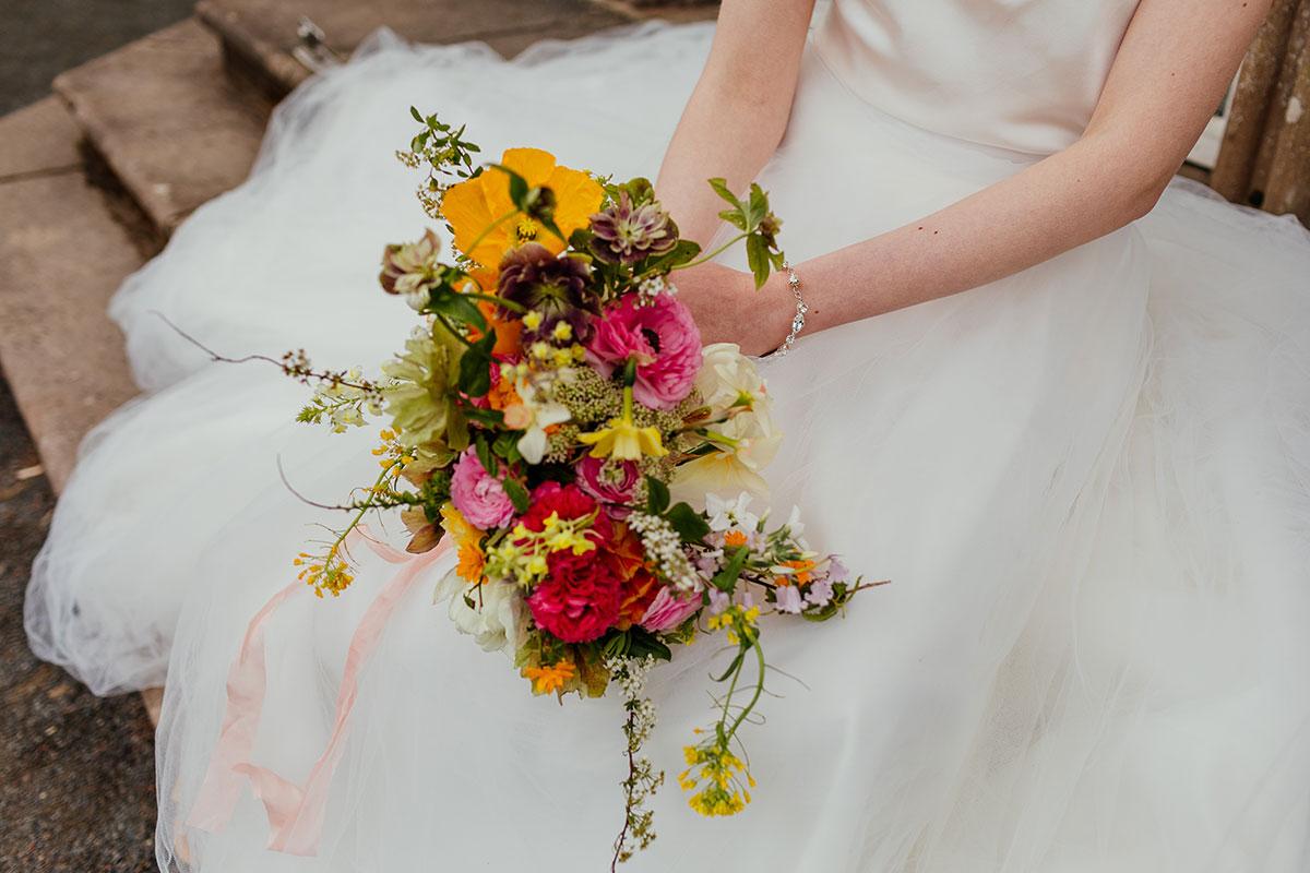 a bride's hands holding a multi-coloured bridal bouquet by Briar Rose Design