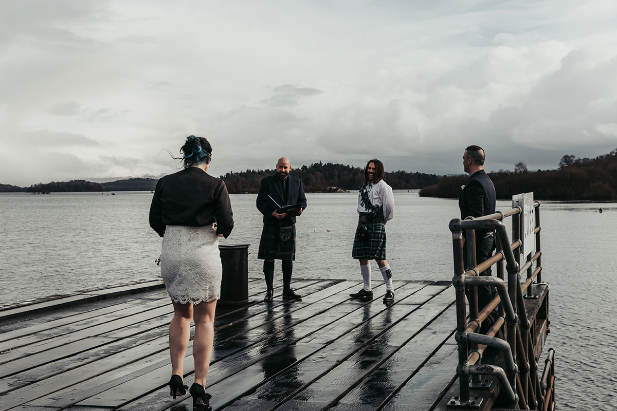 four people standing on the end of the pier in Luss Loch Lomond for an outdoor lockown wedding ceremony