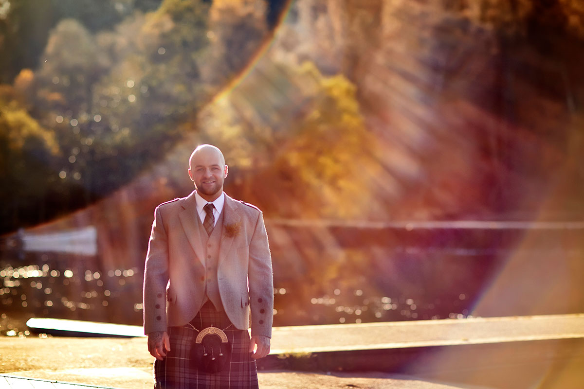 groom wearing a kilt walking along the shore of a loch in Scotland in the sunshine