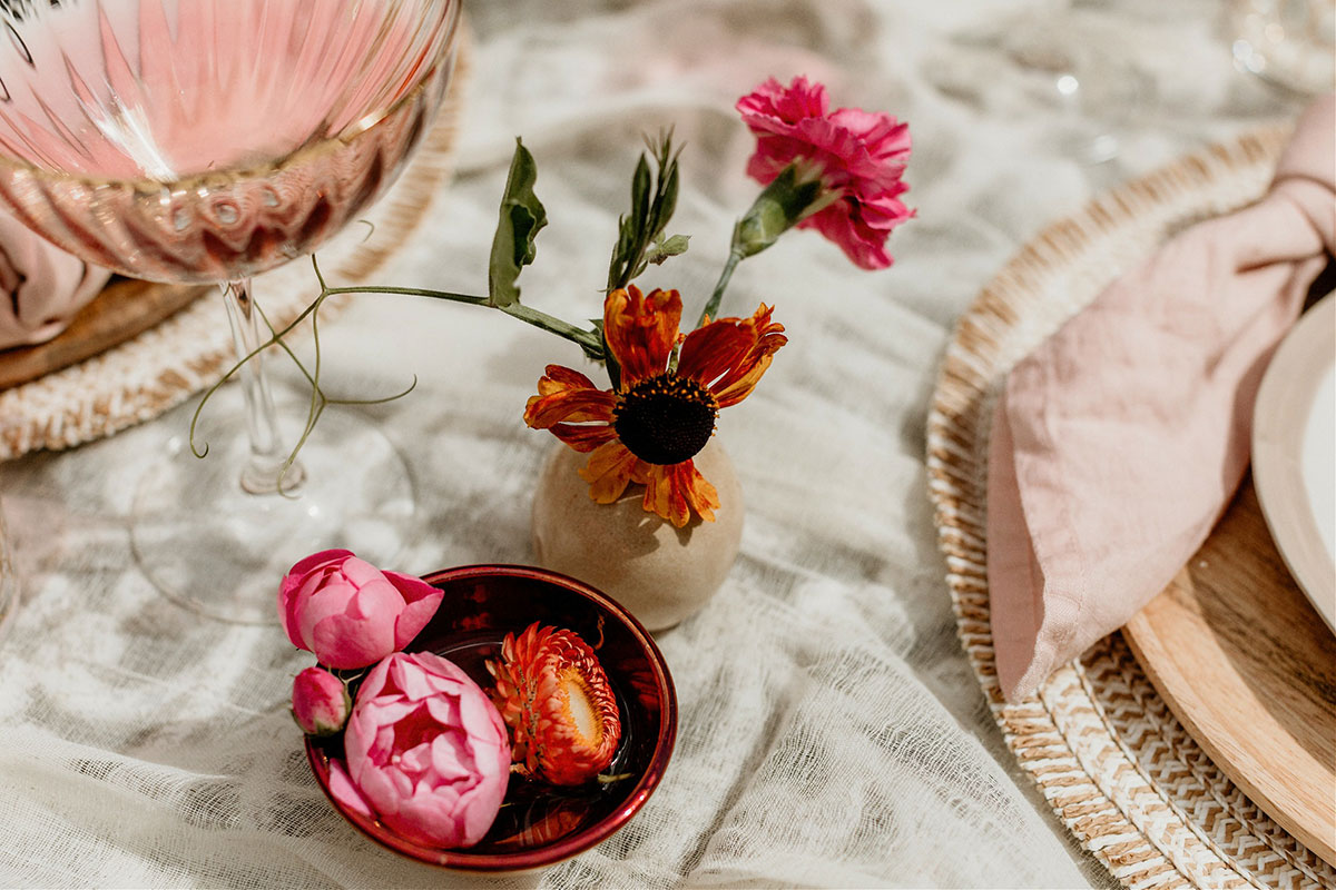 linen tablecloth styled wtih pink and orange miniature flower arrangements in jar and bowl