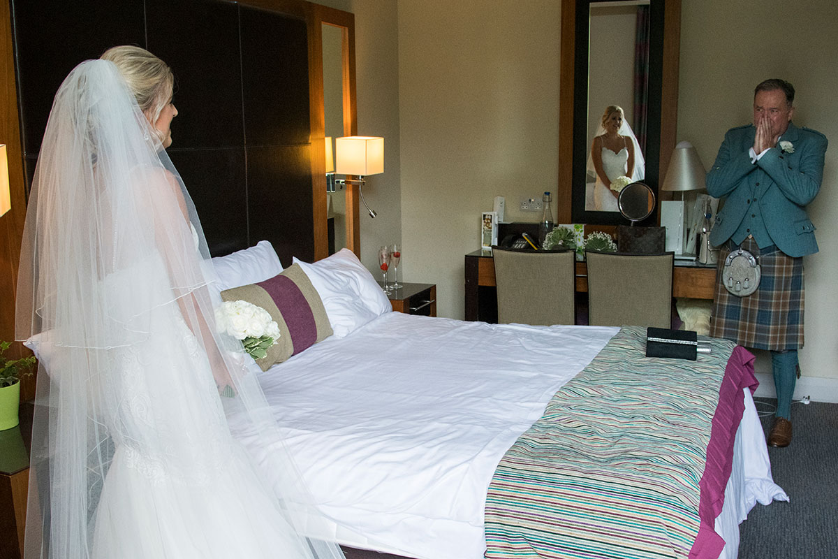 a father of the bride getting emotional in a hotel room as a bride shows him how she looks on her wedding day