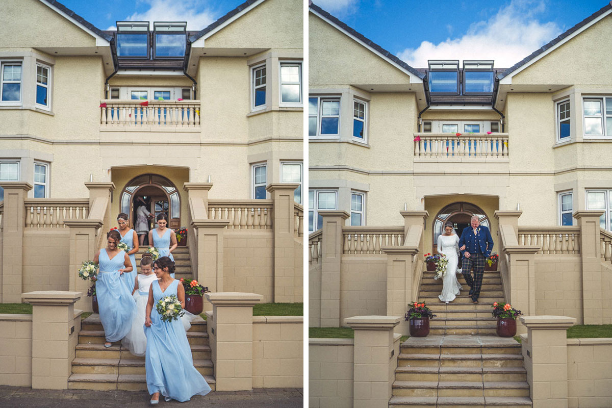 bridesmaids wearing blue walking down stairs outside a cream two storey house and bride leaving same house on arm of father