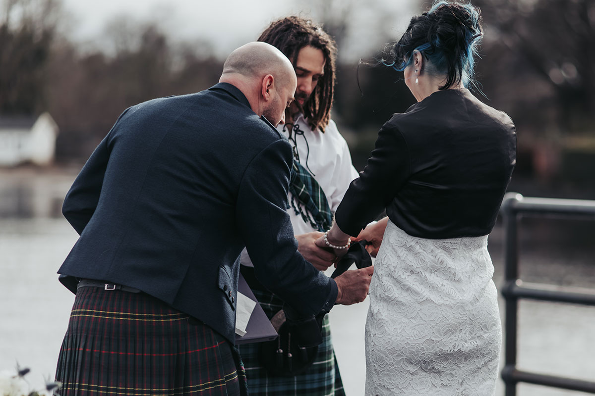 male wedding celebrant performing handfasting ceremony with bride and groom on Luss Pier