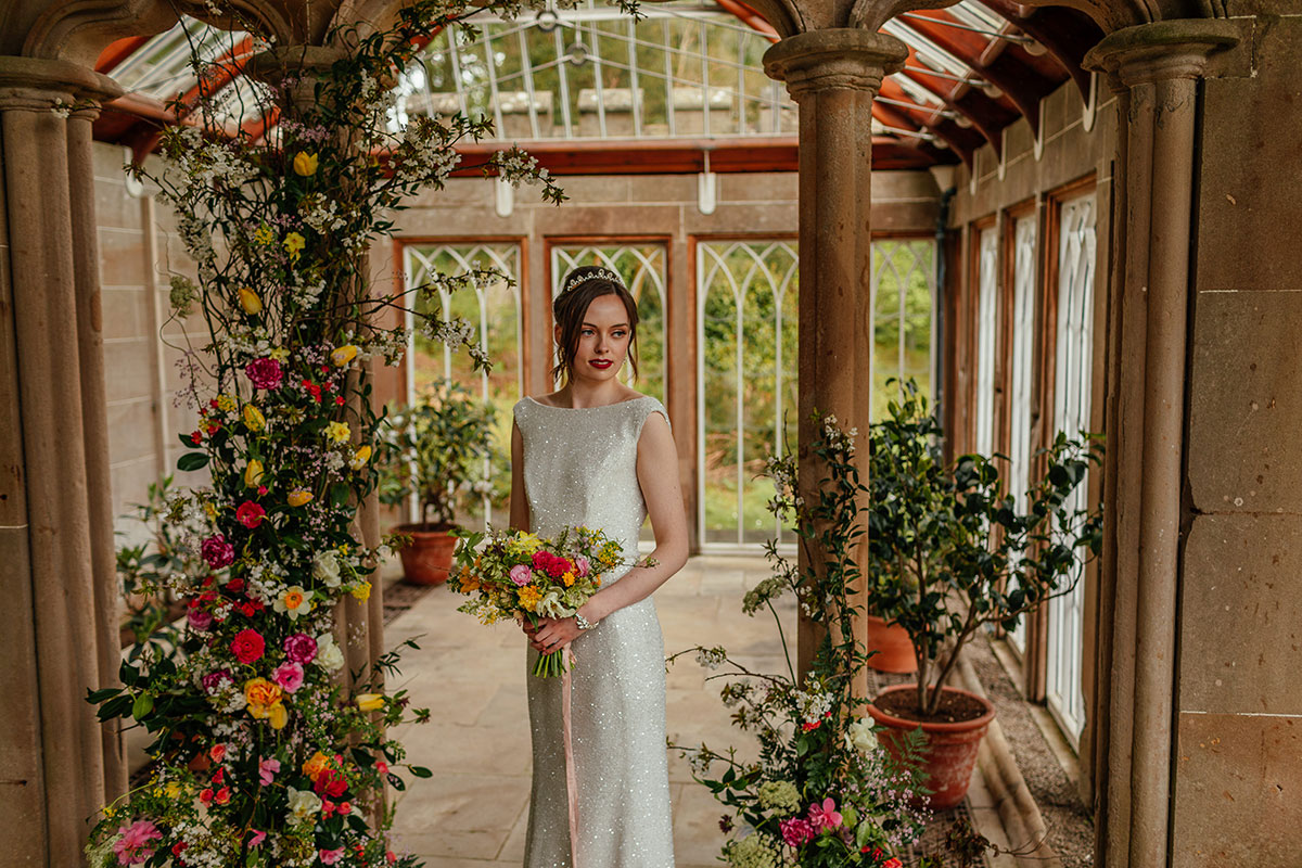 Bride standing in the Camellia House Culzean Castle wearing a sparkly wedding dress by Flossy and Dossy