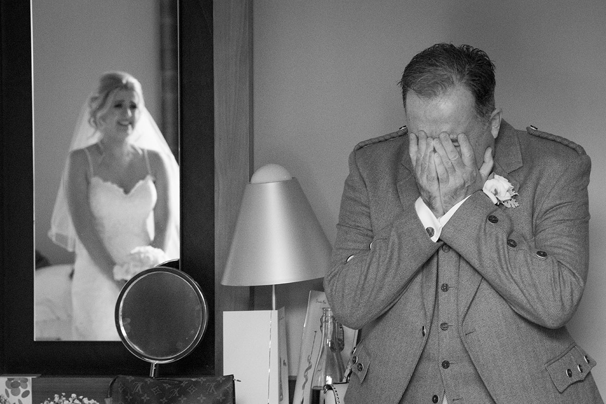 black and white image of emotional dad and bride looking at him reflected in mirror
