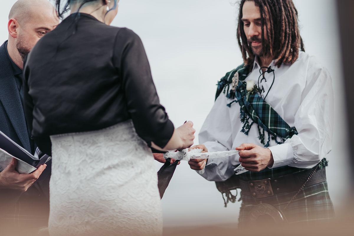 bride and groom tying tartan handfasting ribbon on Luss Pier