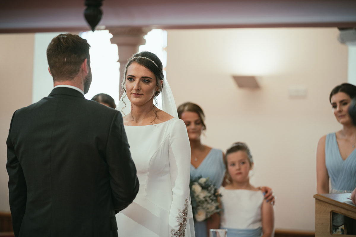 bride looking at groom during church wedding ceremony with bridesmaids and flower girl watching on