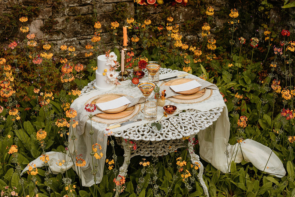 small white table set for wedding for two surrounded by yellow and orange flowers in summer woodland setting