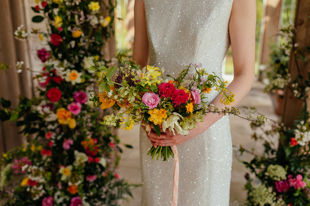 bride holding a rainbow-coloured wedding bouquet of flowers by Briar Rose Design