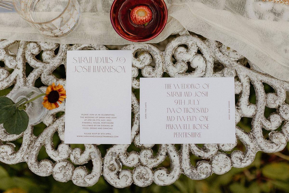 white wedding stationery by Aura Studio on ornate white table