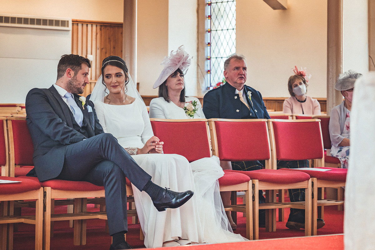 bride and groom sitting on red seats in a church with other guests sitting in background