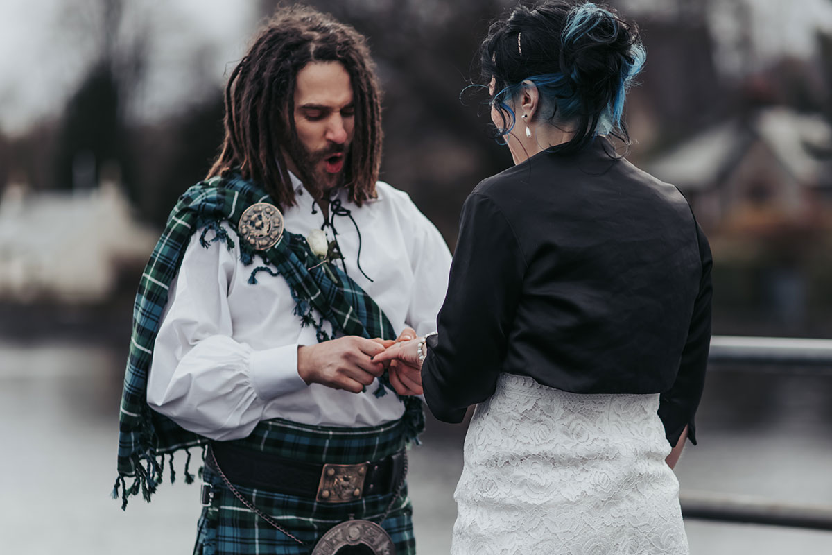 groom with dreadlocks and tartan fly plaid making funny face while trying to put wedding ring on bride during wedding ceremony on Luss Pier