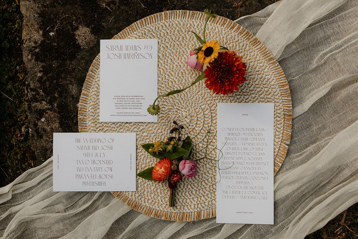 wedding stationery by Aura Studio on rattan placemat with buttonhole and flowers by Adelaide's Secret Garden