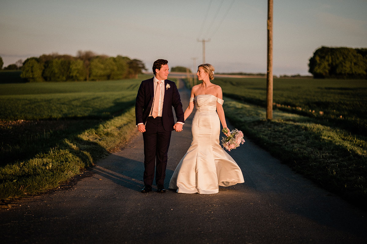 Bride and groom holding hands walking along a country road at sunset looking into each other's eyes