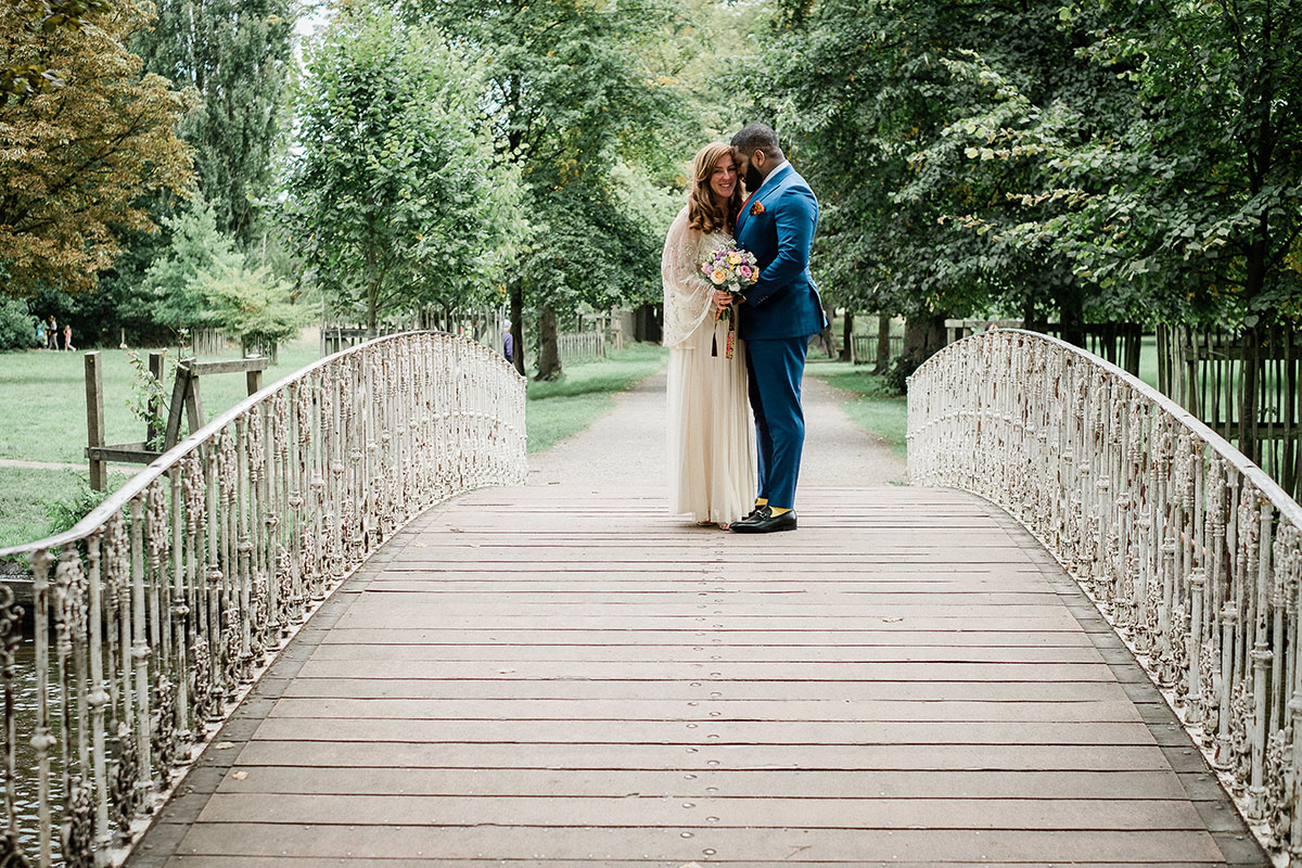 Bride and groom hugging while standing on a wooden and wrought iron bridge with trees in background