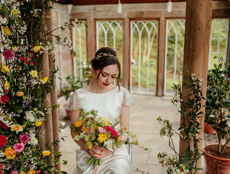Bride sitting down holding a multi-coloured bouquet of flowers in the Camellia House at Culzean Castle