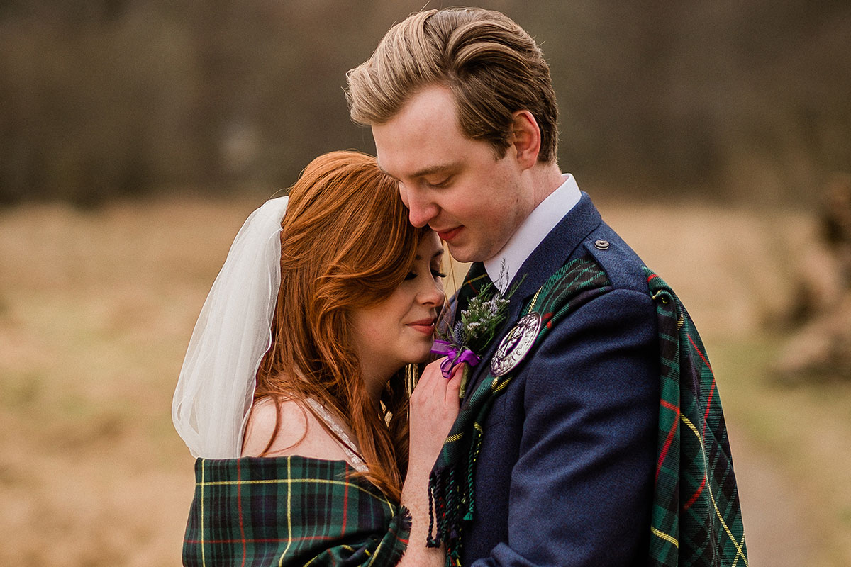 Bride with red hair and tartan shawl around shoulders being hugged by a blond groom wearing tartan fly plaid and navy jacket standing in a field