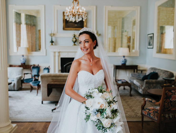 Bride looking over shoulder carrying white bouquet and wearing makeup by I Do Make Up by Geo Kane