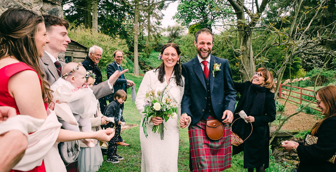 Smiling bride and groom holding hands while guests throw confetti at them in woodland