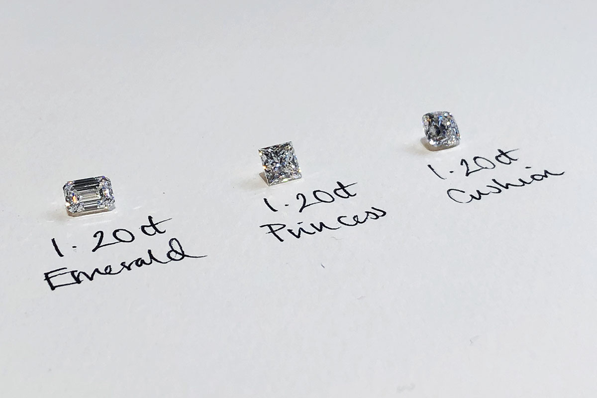 Three 1.2 carat diamonds in emerald, princess and cushion cut with hand written note below each from Laings