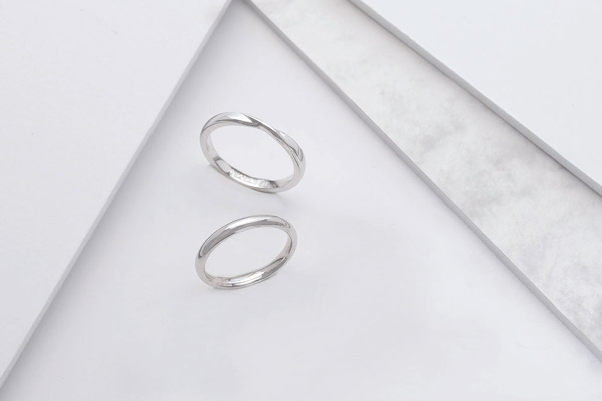 Two platinum wedding bands on triangle background by Laings