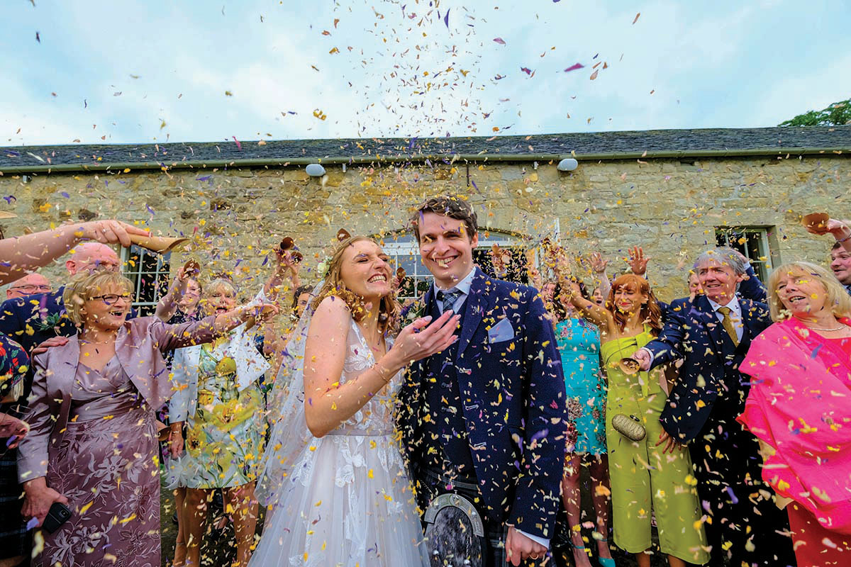A couple stands under a shower of confetti thrown by their guests