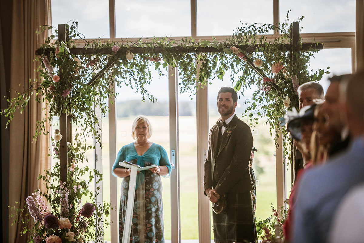 A groom looks back down the aisle as the bride arrives