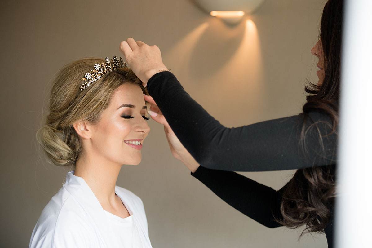 A hairstylist fixes a bride's hair while she's getting ready