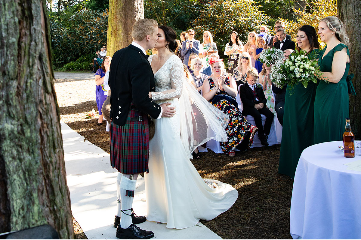 A couple kiss after saying 'I do' underneath trees