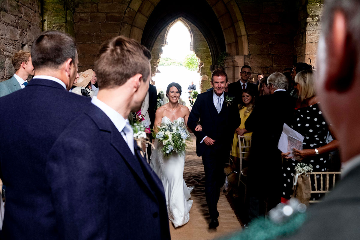 A groom looks at a bride as she walks down the aisle with her dad